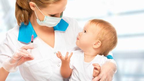 врач держит ребенка на руках