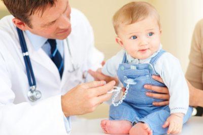 врач осматривает маленького ребенка
